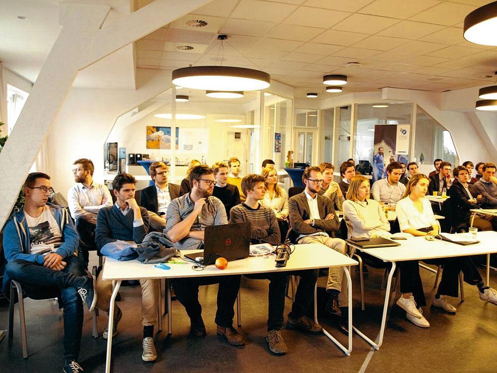 De deelnemers luisteren naar de introductiespeech.